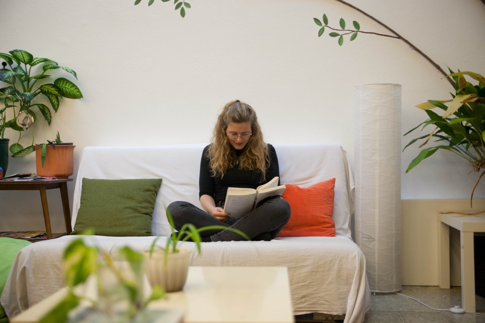 Wohnzimmerecke im Veranstaltungsraum des schubertNESTs wird von einer Studentin zum Lesen benutzt